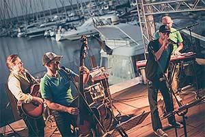 Livekonzert in einem Hafen. Band auf Bühne und im Hintergrund der hafen mit den Segelbooten